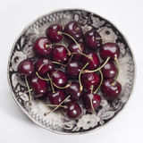 Cherries. Some cherries in an antique plate royalty free stock images