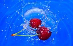 Cherries splashing Stock Images