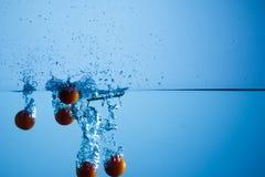 Cherries splashing water royalty free stock photography