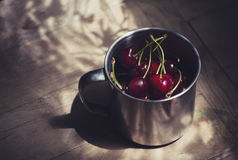 Cherries in a steel cup on wooden table Royalty Free Stock Photos