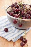 Cherries in a strainer. Fresh picked cherries sit in a wire mesh colander on a blue and white striped towel after being washed Stock Images