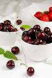 Cherries and Strawberries. In the white bowls Royalty Free Stock Image