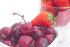 Cherries and strawberry in a ceramic and glass bowl Stock Images