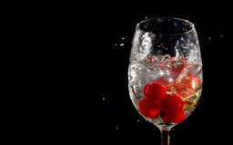 Cherries and Strawberry in glass of water. Cherries and Strawberry dropped into glass of water on isolated black background Stock Photography