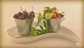 Cherries tins. Red colorful luscious cherries displayed in silver tins and white ceramic dish stock image