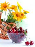 Cherries in a transparent bowl and  flowers. Cherries in a transparent bowl and yellow flowers Royalty Free Stock Photography