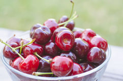 Cherries in transparent bowl. Isolated on wood background Stock Photo