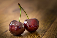 Cherries. Two cherries on wooden table Stock Photography