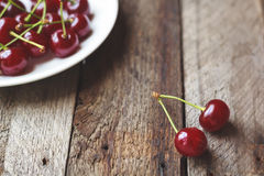 Cherries on vintage wooden table in plate. Cherries on vintage wooden table in white plate royalty free stock photos