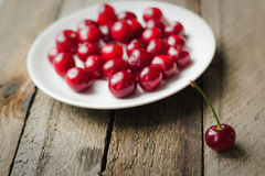 Cherries on vintage wooden table in plate. Cherries on vintage wooden table in white plate royalty free stock image