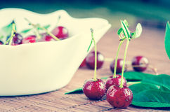 Cherries in water droplets. Three cherries on the table in the water droplets Stock Image
