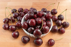 Cherries in a white bowl on the wood tabel Royalty Free Stock Photos