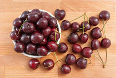 Cherries in a white bowl on the wood tabel Stock Image