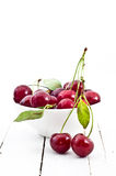 Cherries in white china bowl. White china bowl of fresh cherries with stems and leaves on white painted wooden tabletop royalty free stock photography