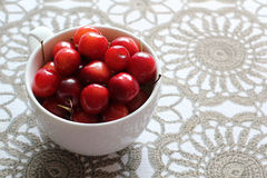 Cherries in white cup on desk. Stock Images