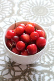 Cherries in white cup on desk. Stock Photos