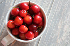 Cherries in white cup on wooden grey desk. Stock Images