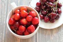 Cherries in white cup on wooden grey desk. Stock Image