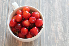 Cherries in white cup on wooden grey desk. Royalty Free Stock Photography