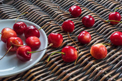 Cherries in the white dish and on the wicker backround Royalty Free Stock Photo