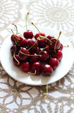 Cherries in white plate on desk. Royalty Free Stock Photography