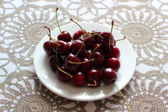 Cherries in white plate on desk. Royalty Free Stock Photo