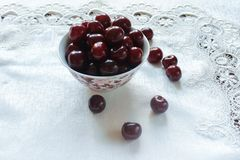 Cherries on a white plate and white tablecloth Stock Photos