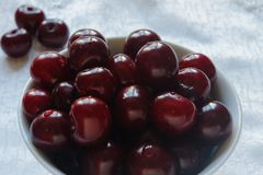 Cherries on a white plate and white tablecloth Stock Photography