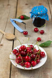 Cherries in a white plate on wooden background. With a jar of cherry jam royalty free stock photography