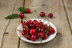 Cherries in a white plate on wooden background. Selective focus royalty free stock photos