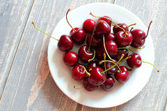 Cherries in white plate on wooden grey desk. Royalty Free Stock Photography