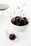 Cherries white spoon and bowl, sherry glass. Single cherry on a white china spoon, a cherries group in a small round white bowl and a sherry glass with a spoon royalty free stock photos