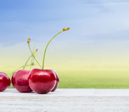 Cherries on white table on sky background Royalty Free Stock Photo