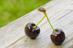 2 cherries on wood. Background Stock Photos