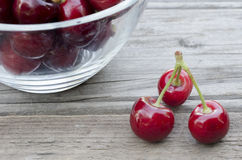 Cherries on wood and in bowl. Isolated on wood background Royalty Free Stock Images