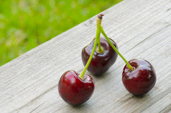 3 Cherries on wooden background. 3 Cherries  on wooden background Stock Photo