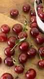 Cherries on wooden chopping board and in bowl. Several cherries on wooden chopping board and table and in a white bowl Stock Image