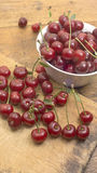 Cherries on wooden chopping board and in bowl. Several cherries on wooden chopping board and table and in a white bowl Royalty Free Stock Photo