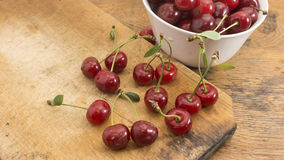 Cherries on wooden chopping board and in bowl. Several cherries on wooden chopping board and table and in a white bowl Royalty Free Stock Image