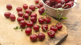 Cherries on wooden chopping board and bowl. Several cherries on wooden chopping board and table and in white bowl Royalty Free Stock Image