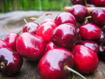 Cherries on a wooden table. Wet cherries on an old country table after rain Stock Photo