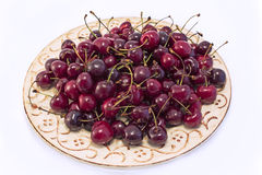 Cherries on the yellow plate Stock Photos