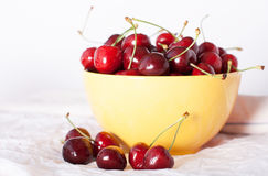 Cherries in a yellow plate. On the table Stock Photos