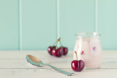 Cherries yogurt. A jar with cherry yogurt and some cherries in a white wooden table with a robin egg blue background. Vintage style Royalty Free Stock Images