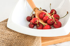 Cherries and zucchini on wood and white fabric Stock Photos