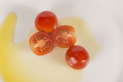 Cherrt tomatoes sliced and whole. Cherry Tomatoes on a plate with olive oil Royalty Free Stock Photos