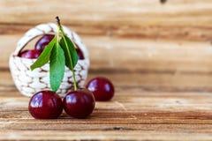 cherry świeże Dekoracyjny kosz z czereśniowymi jagodami na drewnianym tle obrazy royalty free