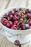 Cherry. In a sieve on a wooden table Royalty Free Stock Photos