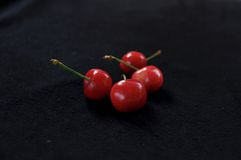 Cherry. Several of the cherry on the black cloth Stock Images