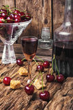 Cherry alcohol drink. Homemade alcohol tincture from summer cherry berries Stock Image